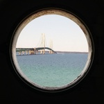 The Mackinac Bridge through the porthole window of the Old Mackinac Point Lighthouse tower.