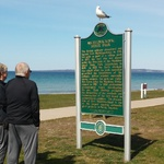 A seagull watches sightseers reading from a historical marker.